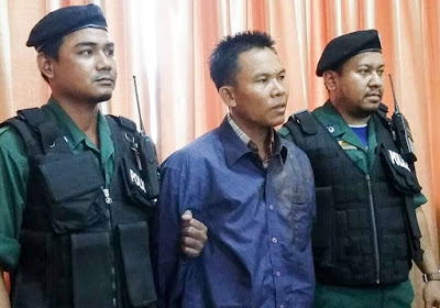 Eout Ang stands at a press conference yesterday in Phnom Penh flanked by police after he was arrested for shooting political analyst Kem Ley. Photo supplied