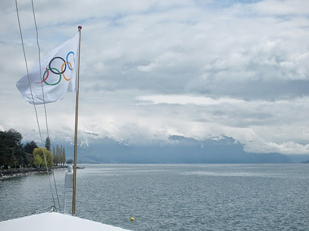 The Olympic flag, Lake Geneva and a view of the Alps in Lausanne, Switzerland
