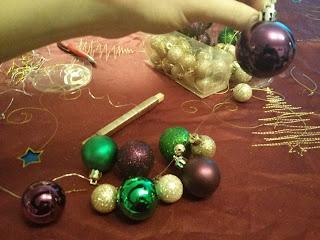 A gömbök fűzése a karácsonyi koszorúhoz