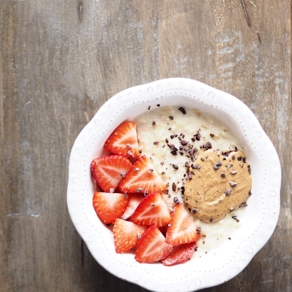 porridge with strawberries, almond butter and cacao nibs sprinkled on top - breakfast to be eaten before running on race day