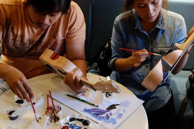 Nat and Deah paint their ukuleles at UkeHUB Kafe