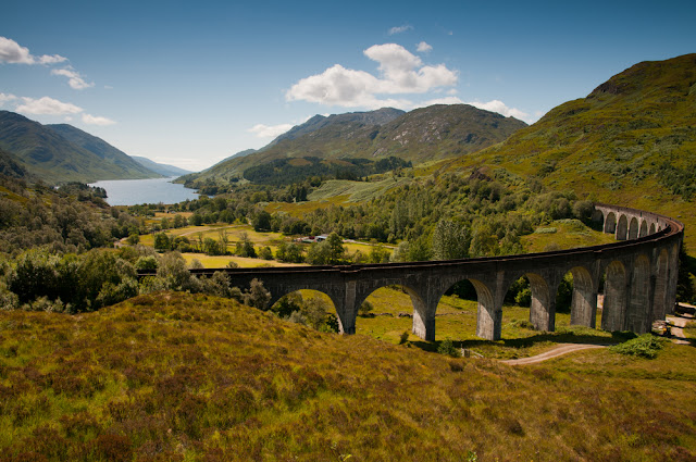 A view of the Glenfinnan Viaduct in Scotland with rolling hills in the background