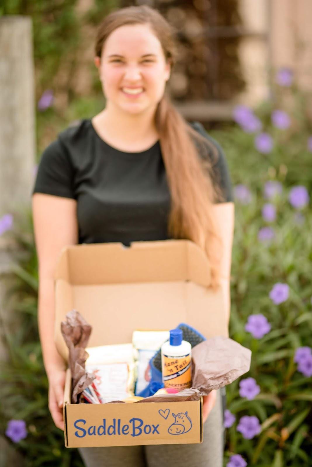 Brunette girl holding open Saddlebox horse subscription box items