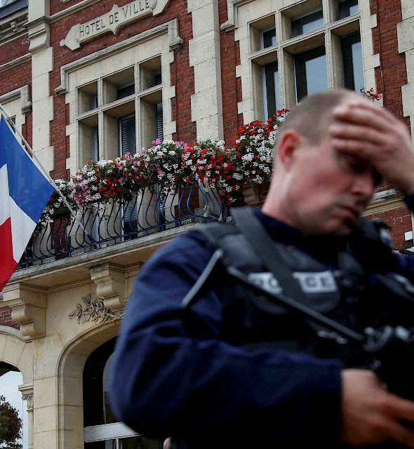 """Policial diante da prefeitura de Saint-Etienne du Rouvray após o crime anunciado. D. Amel Nona: """"vós vos tornareis vítimas do inimigo que recebestes em vossa casa"""""""