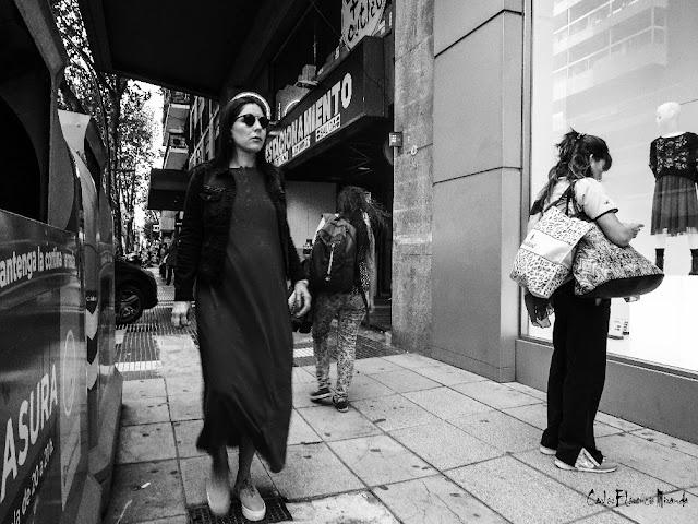 Foto callejera en Blanco y Negro.Mujer con gafas caminando.