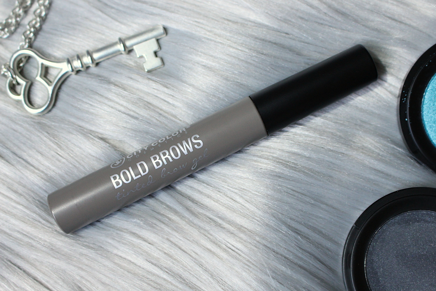 City Color Cosmetics Tinted Brow Gel In 'Taupe' is laying on a furry rug