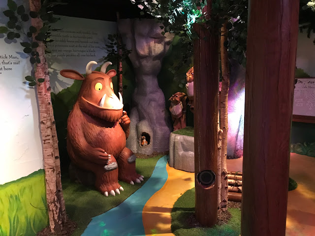 A model of the Gruffalo surrounded by trees and a painted stream and grass