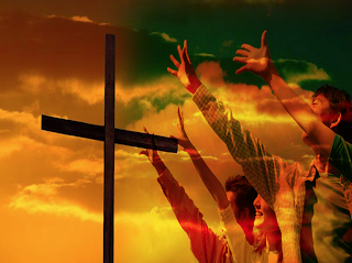 People praising with arms outstretched toward the cross