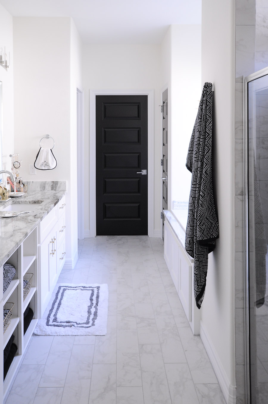Black doors make a bold statement against white walls in this chic white & gold master bathroom suite.