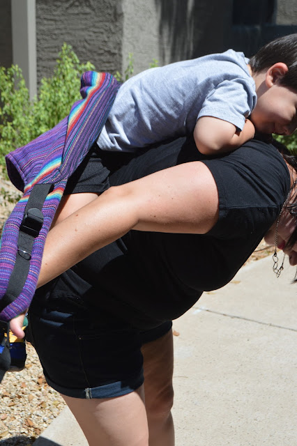 Woman is seen sliding her arms into shoulder straps of purple onbu with toddler on her back