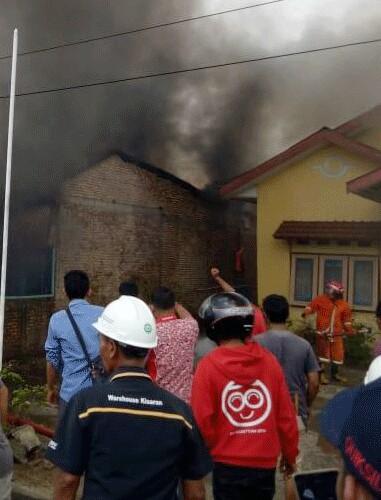 Warga dan petugas pemadam kebakaran memadamkan api.