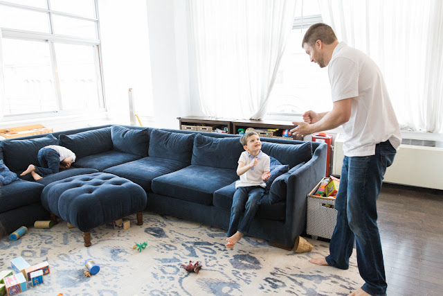 son and dad play dinosaurs on the couch