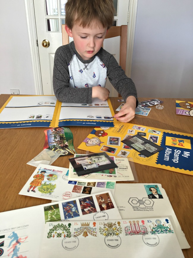 Christmas-gift-guide-2018-boy-sticking-stamps-from-stamp-active-with-contents-of-kit