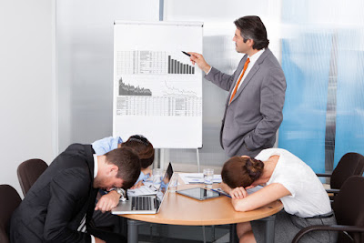 a presenter is looking at his flip chart while his audience has fallen asleep