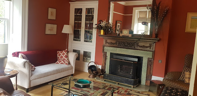 Guest Lounge of Sunnybank Guesthouse with chic sofas, a large ornate fireplace and bookshelves.
