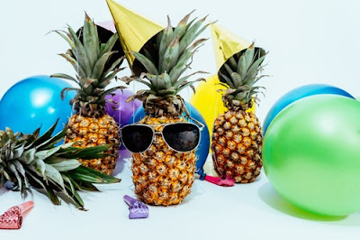 Three pineapples wearing party hats, and one wearing sunglasses, surrounded by colourful balloons and party items, by Scott Webb Photography