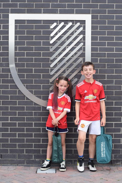 boy and girl in manchester united kit outside Hotel Football