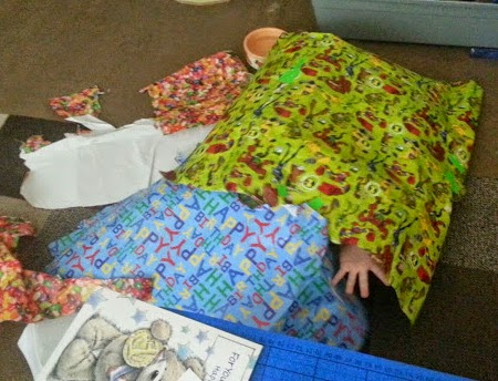 4 year old hiding in wrapping paper