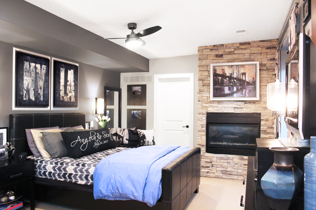 Bedroom with Stacked Stone Fireplace and Framed Canvas Art Above Bed