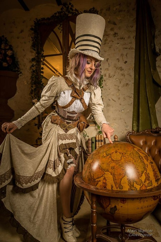 Woman dressed in steampunk clothing as a steampunk mad hatter/magician with tan, white, and brown. Women's steampunk clothing, fashion, costume and cosplay