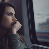 woman looking out car or train window - depression and addiction