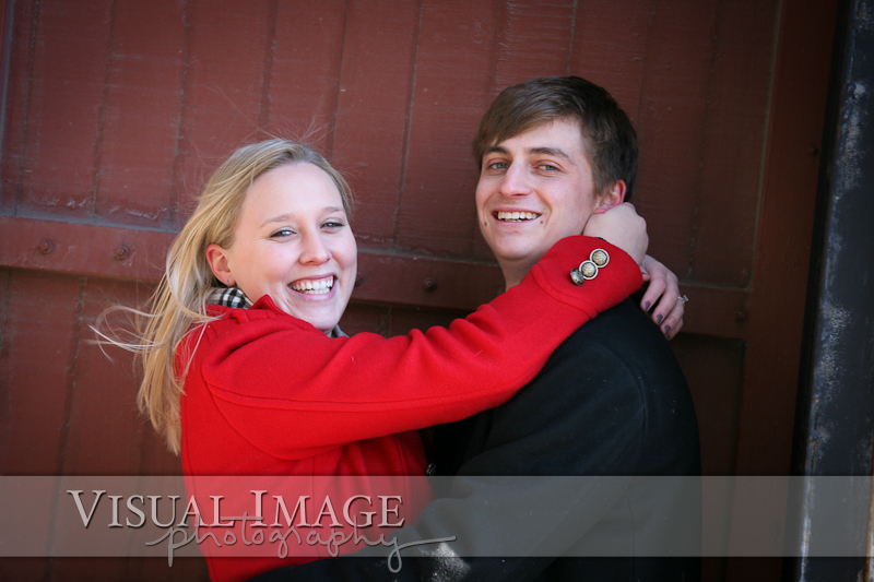 Engaged couple in winter coats looking at camera and smiling