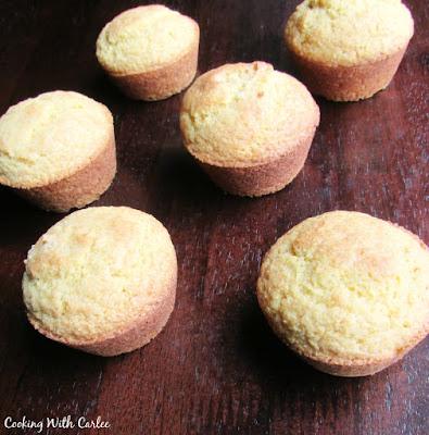 golden corn muffins on dark wood background