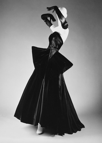 Black Evening Gown with asymmetrical hemline and bustle designed by Christian Dior for Fall/Winter 1949-1950 collection displayed on mannequin
