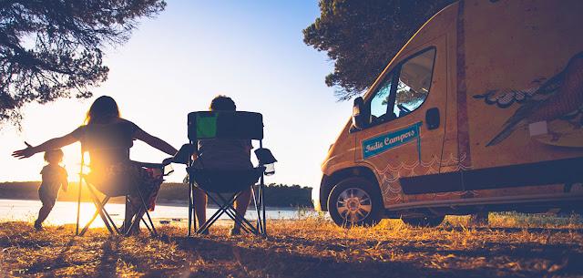 Uma carrinha amarela da Indie Campers e uma família