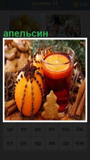 лежит апельсин, рядом стоит стакан с чаем и корица на столе