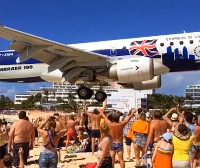 Tourist Captures The Incredible Moment A Plane Passes Just A Few Feet Above A Crowded Beach.