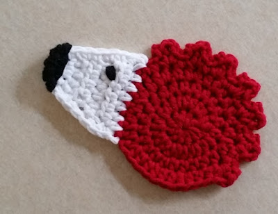 A 'hedgehog' motif consisting of a red circle crocheted in the round for the body with a jagged border across the top for spines; a white triangular face with black embroidered eye and nose.