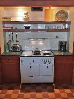 Restored Vintage Chambers stove model 90C highback set in vintage kitchen with subway tiles and cork floor.