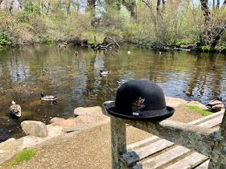 a tranquil duck pond with a bowler hat on a fence in the foreground