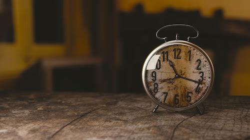 Relógio-despertador antigo de mesa, marcando onze horas e dezessete minutos, sobre um móvel de madeira velha