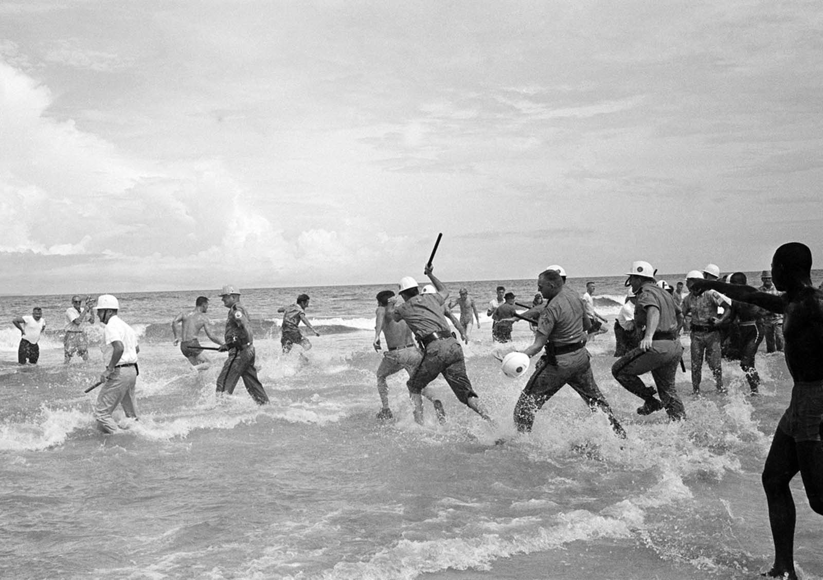 A state police officer with club in hand overtakes a white segregationist, as African Americans attempted to swim and were attacked by a large group of whites at St. Augustine Beach, Florida, on June 25, 1964. The state police arrested a number of whites and African Americans.
