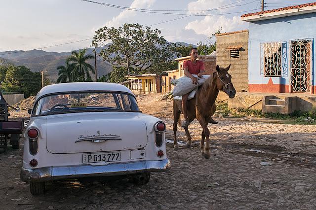 Un homme à cheval passe devant une vieille voiture américaine à Trinidad (Cuba)