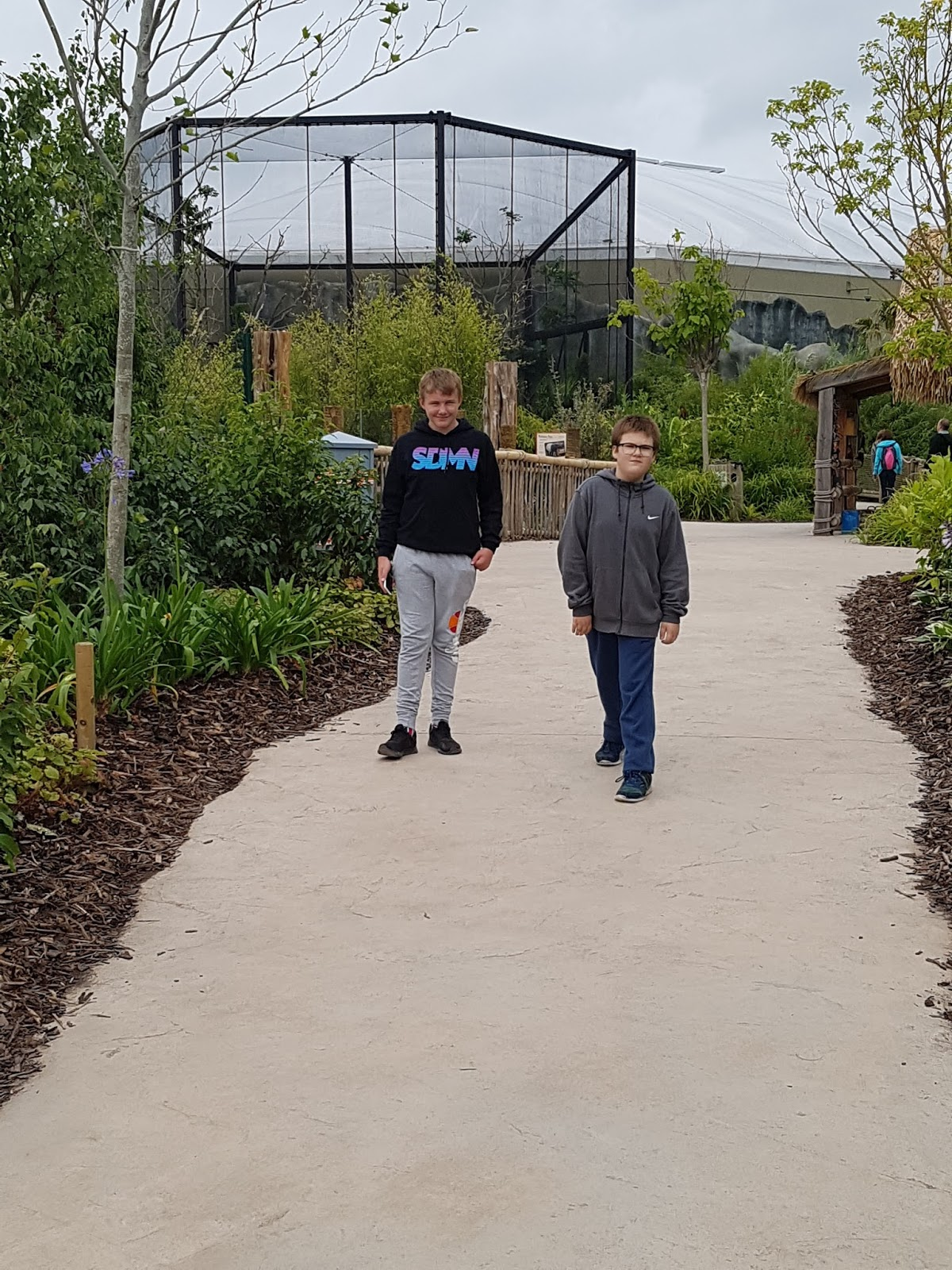 Ben and Ryan walking along a walkway between enclosures, no animals seen, no other people in photo showing how empty it was