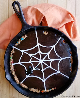 monster skillet cookie topped in fudge frosting with icing spider web