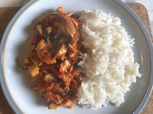 A close up of shredded chicken and vegetables on one side of the plate and fluffy white rice on the other side