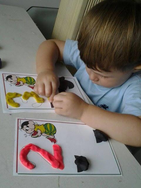 O pequeno Rafael realizando atividade com massinha e fichas de trabalho