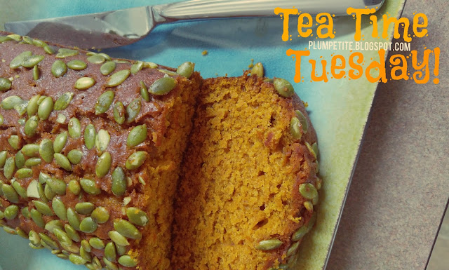 Close up of a pumpkin bread loaf with pumpkin seeds on top sitting on a square blue and green plate with a plain silver butter knife next to the bread on the plate. Also has Tea Time Tuesday and PlumPetite.blogspot.com in orange and white text in the upper right corner.