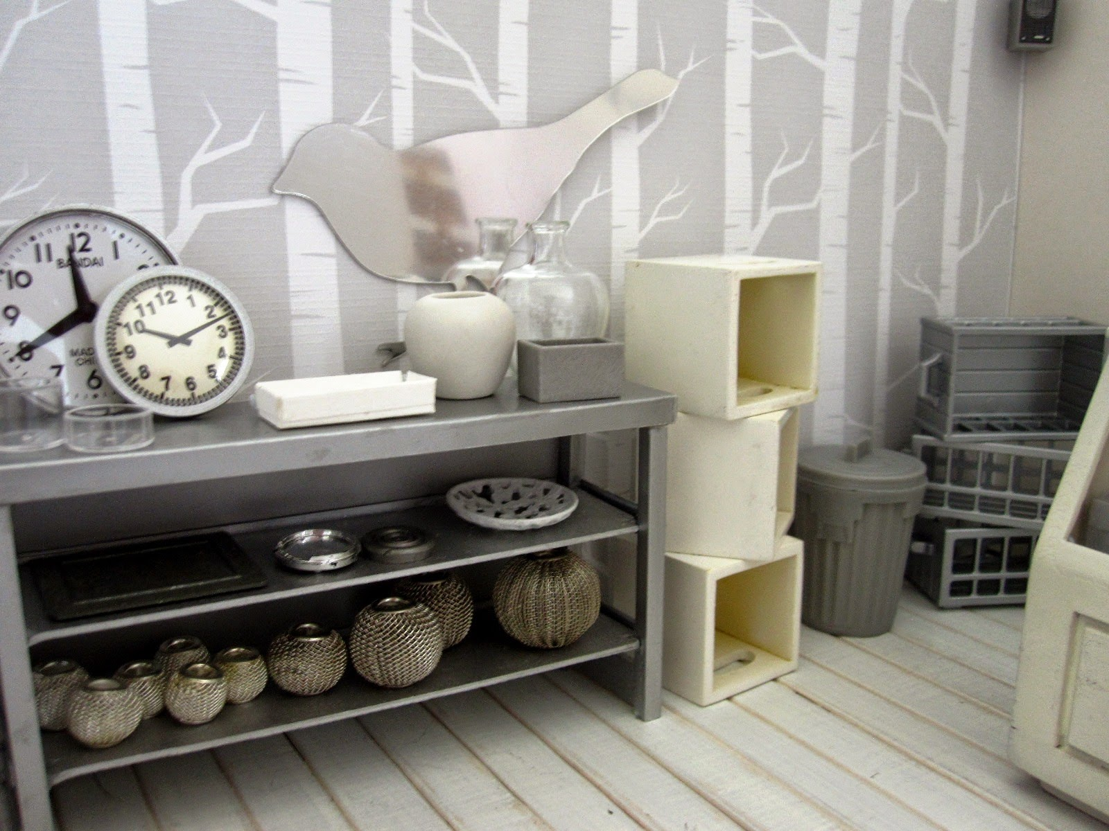 View of a modern dolls' house miniature homeware shop in grey and white. On display is  a grey metal shelving unit with various grey-coloured decor pieces. To the right is a pile of white storage boxes, a grey trash can and a pile of grey storage baskets.