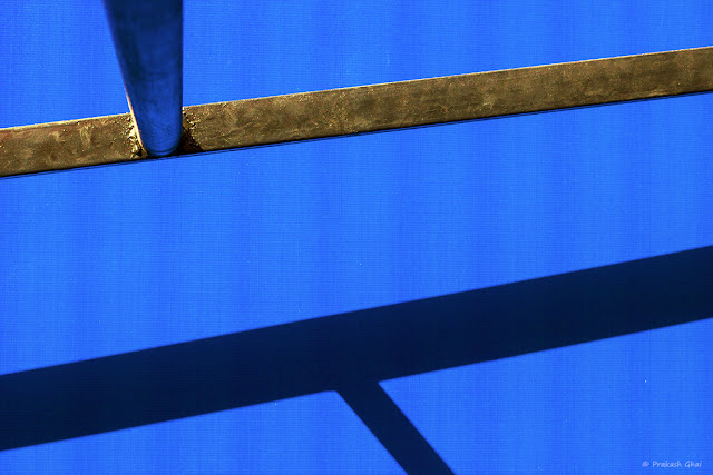 Minimalist Photo of T point made out of a ladder lying in front of a blue tent at Jaipur Literature Festival 2016