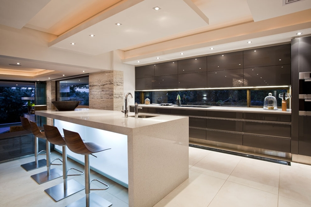 Kitchen with lighted up bar and three chairs in the Contemporary South African SGNW House by Metropole Architects