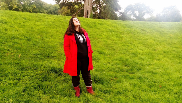 Woman in a red raincoat, looking up disdainfully at the rain.