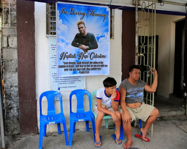 Image Attribute: Relatives sits in-front of a poster of Neptali Celestino, who was killed in a police anti-drugs operation, at his wake in Pasig city, metro Manila, Philippines September 15, 2016. Picture taken September 15, 2016. REUTERS/Romeo Ranoco