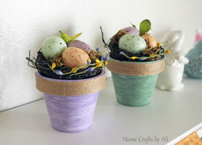 Springtime decorations of painted flower pots with egg nests