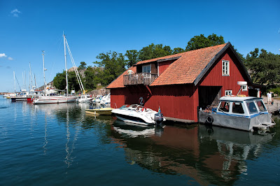 pic of red Swedish summerhouse at waterside surrounded by boats and yachts