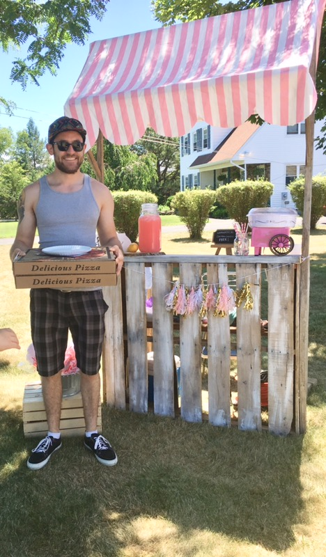 man holding pizza in front of lemonade stand at Pop Up Shop